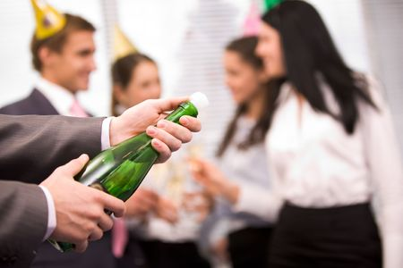corporate woman: Image of male hands holding bottle of champagne and uncorking it