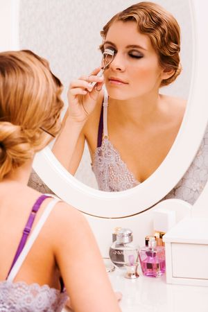 Image of pretty female looking in mirror while curling her eyelashes photo