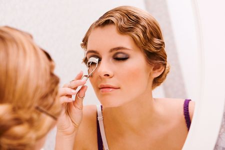 curling: Image of pretty female looking in mirror while curling her eyelashes