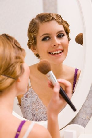 Image of pretty female looking in mirror and doing makeup photo