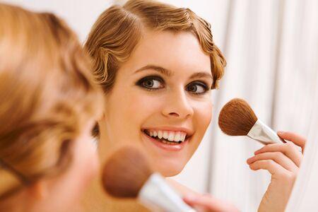 polvos: Imagen de mira en el espejo y haciendo maquillaje muy femenino Foto de archivo