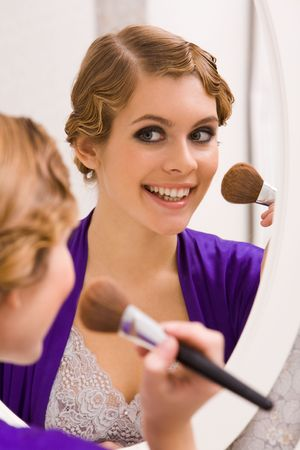 Image of pretty female looking in mirror and doing makeup Stock Photo - 6107337