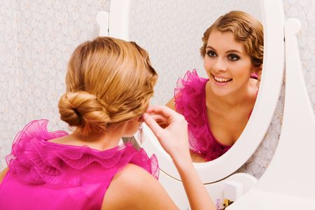Image of pretty female looking in mirror and putting on earrings photo
