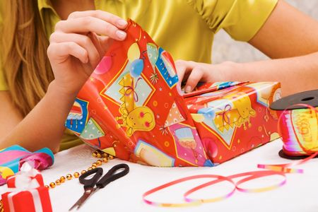 xmas crafts: Close-up of female hands wrapping Christmas presents