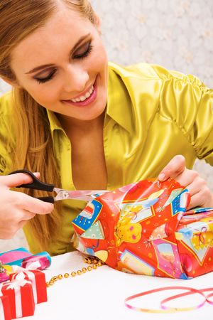 Happy woman wrapping Christmas presents before holiday photo