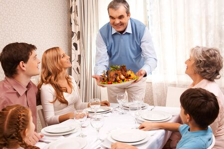 family dinner: Portrait of big family sitting at festive table and looking at aged man with cooked turkey