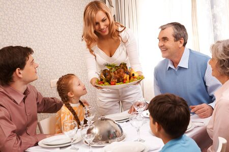 Portrait of big family sitting at festive table and looking at pretty female with dish of delicious turkey Stock Photo - 6107405