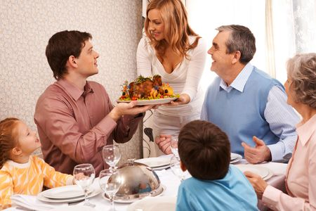 home baked: Portrait of big family sitting at festive table and looking at pretty female with dish of delicious turkey