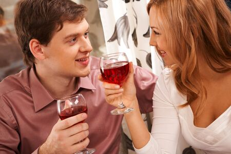Portrait of romantic couple with wineglasses looking at each other photo