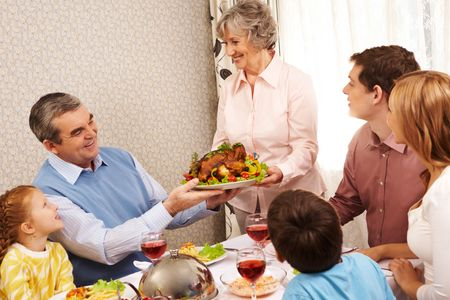 Portrait of big family sitting at festive table and looking at aged female with dish of delicious turkey photo