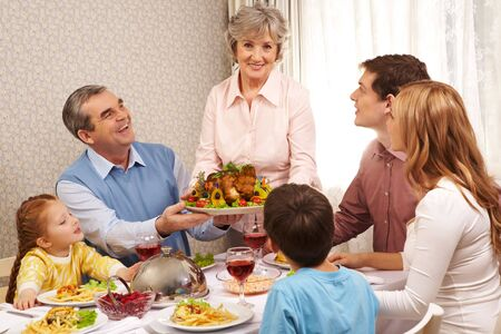 Portrait of big family at festive table looking at aged female with dish of delicious turkey photo