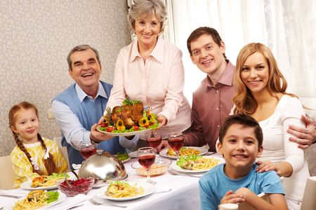 thanksgiving dinner: Portrait of big family sitting at festive table and looking at camera with smiles Stock Photo