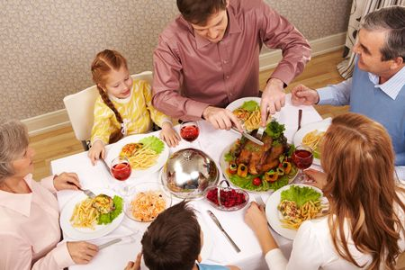 Image of big family sitting at festive table and eating salad and roasted turkey photo