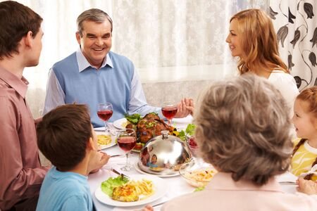 Portrait of happy family sitting at festive table and holding each other by hands photo