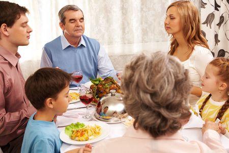 familia cristiana: Retrato de la gran familia sentado en la mesa festiva y mutuamente por manos mientras mantiene orando y