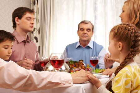 Image of family members praying at festive table while holding each other by hands photo