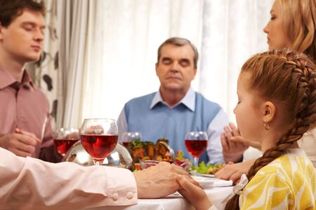 Photo of family members praying at festive table while holding each other by hands photo