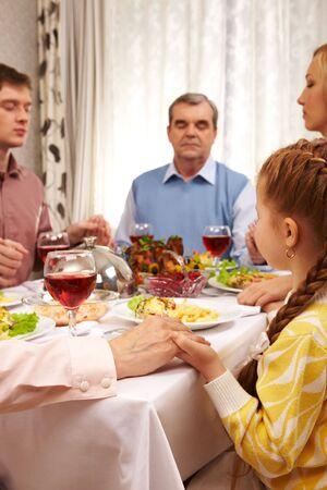 Fotos de miembros de la familia dando gracias a Dios en mesa festiva manteniendo entre sí por las manos Foto de archivo - 6107355