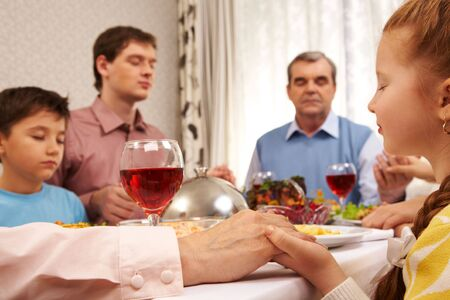 Photo of childish and older person hand holding each other while praying at festive table photo