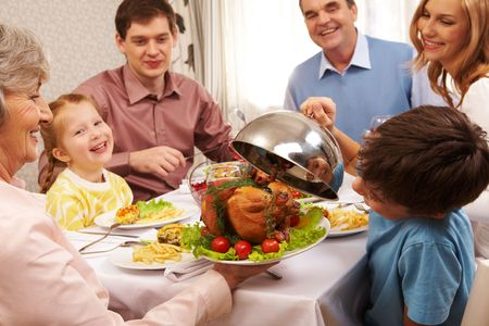 feasts: Portrait of happy family sitting at festive table and holding each other by hands Stock Photo