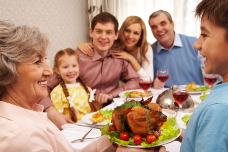 family dinner: Portrait of happy grandmother holding tray with roasted turkey and looking at her grandson