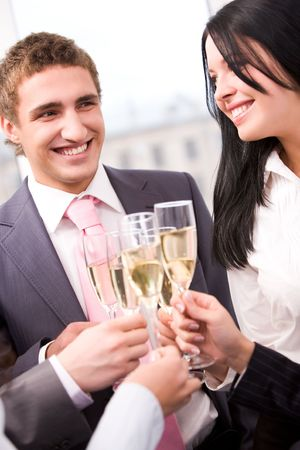 Photo of happy man and woman holding flutes with champagne and smiling while toasting at party photo