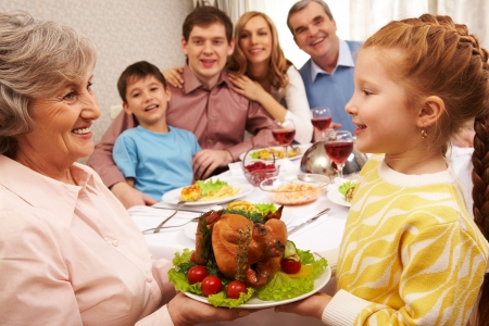 feasts: Senior woman with cooked turkey looking at her granddaughter and both smiling