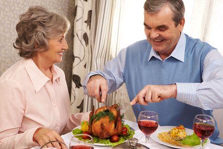 Portrait of senior couple sitting at Christmas table while happy man cutting roasted turkey photo