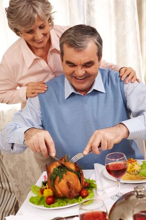 thanksgiving adult: Portrait of senior man cutting roasted turkey with his happy wife behind