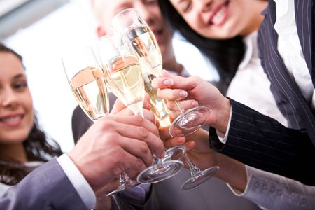 Close-up of friends hands holding glasses with champagne and making cheers photo