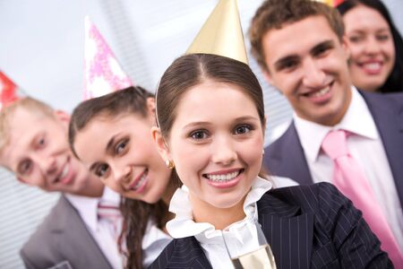 Portrait of joyful female wearing birthday cap looking at camera on background of colleagues  photo