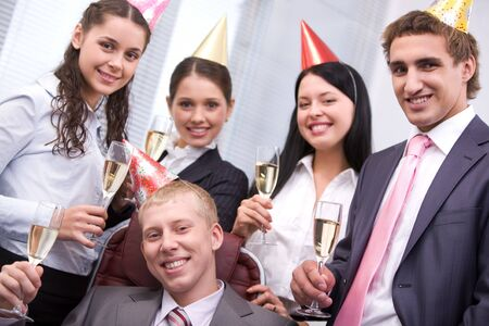 company party: Portrait of joyful male wearing birthday cap looking at camera on background of cheerful colleagues