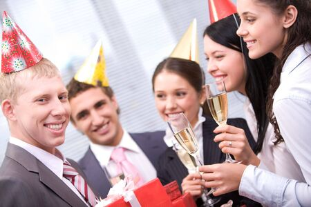Image of happy man holding wrapped giftboxes with cheering friends on background  photo