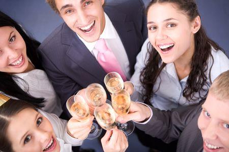 Foto van gelukkige vrienden juichen omhoog tijdens corporate partij