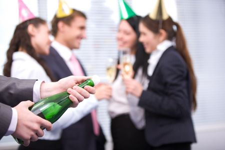 Image of male hands holding bottle of champagne and uncorking it photo