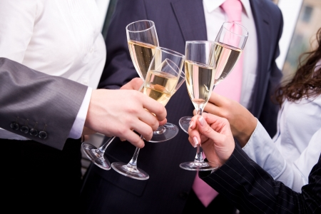 Close-up of human hands cheering up with flutes of sparkling champagne