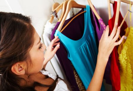 Image of pretty female looking through her wardrobe and choosing smart dress photo