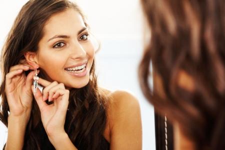 aretes: Imagen de mira en el espejo y poniendo en aretes bastante femenino Foto de archivo