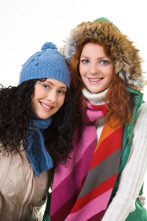 Two friends in warm knitted clothes looking at camera over white background Stock Photo - 6118974