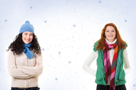 Two friends in warm knitted clothes looking at camera over snowflake background photo
