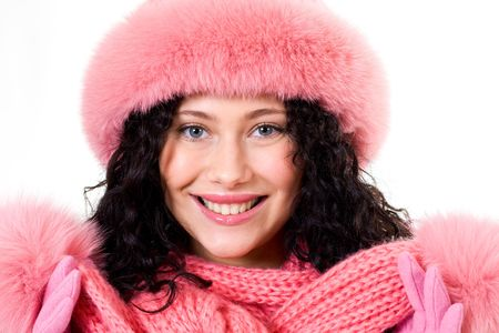 Face of pretty woman wearing pink winter fur cap over white background photo