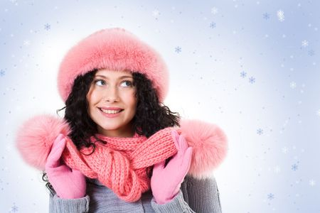 Cheerful woman in pink winter fur cap looking aside with smile on background of snowflakes photo