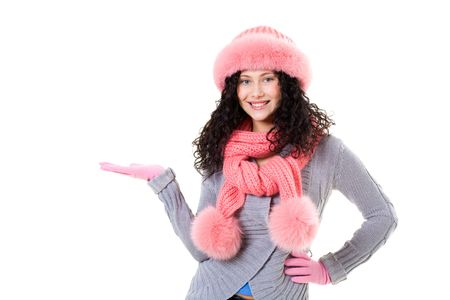 Cheerful woman in pink winter fur cap looking at her palm with smile on white background photo