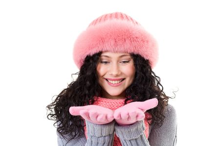 Cheerful woman in pink winter fur cap looking at her palms with smile photo