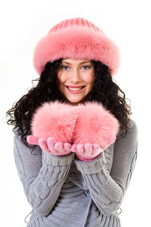 Portrait of cheerful woman in pink winter fur cap looking with smile photo