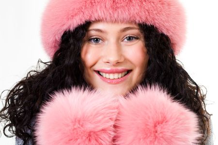 Face of cheerful woman in pink winter fur cap looking at camera photo