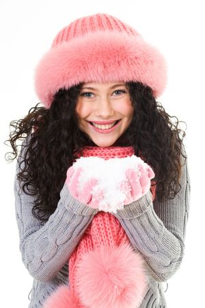 Portrait of cheerful woman in pink winter fur cap holding snow in hands photo