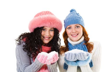Portrait of happy girls holding snow in hands over white background photo