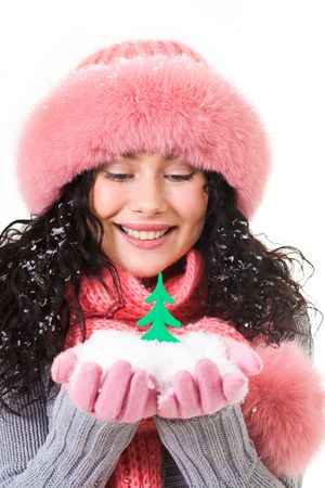 Cheerful woman in pink winter fur cap looking at toy firtree on her palms photo