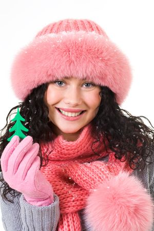 Cheerful woman wearing pink winter fur cap showing toy firtree in her hand photo